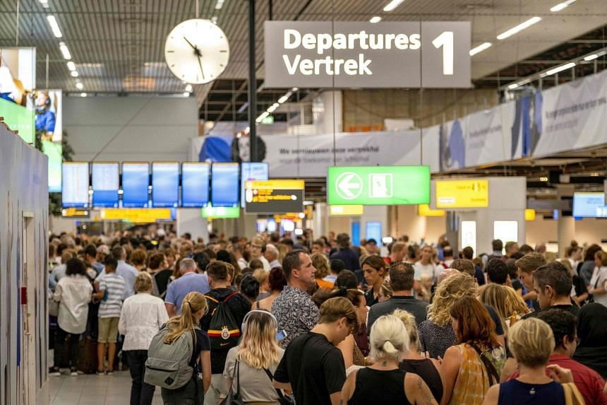 A July 24, 2019 photo shows people waiting in the Schiphol departure hall during a refuelling problem.