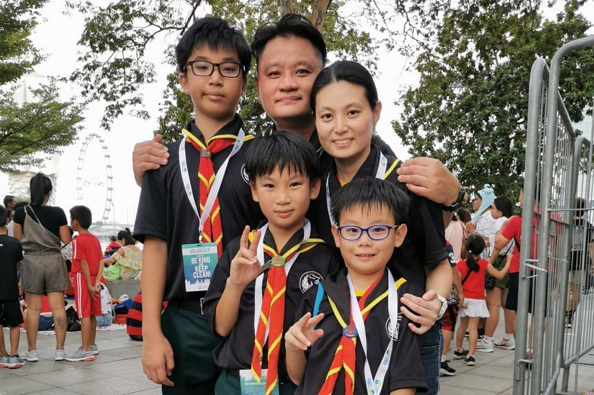 Caleb Teo, with his wife, Shu Yi Ping and their three sons (from left) Isaiah Teo, Zechariah Teo and Jedidiah Teo. The family were among 200 volunteers who combed the periphery of the parade and reminded the public to bin their trash properly.