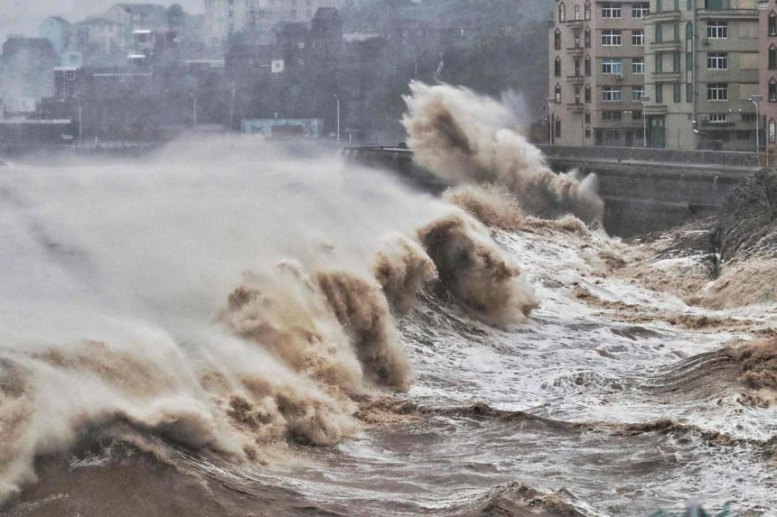 Waves hit a sea wall in front of buildings in Taizhou, China's eastern Zhejiang province on Aug 9, 2019.