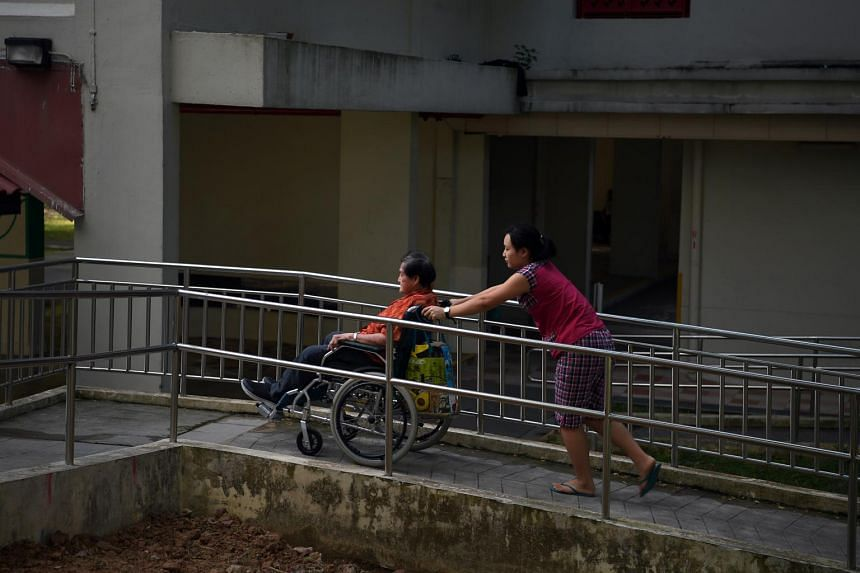 A domestic helper pushing an elderly woman in a wheelchair in Toa Payoh on 9 July 2019.