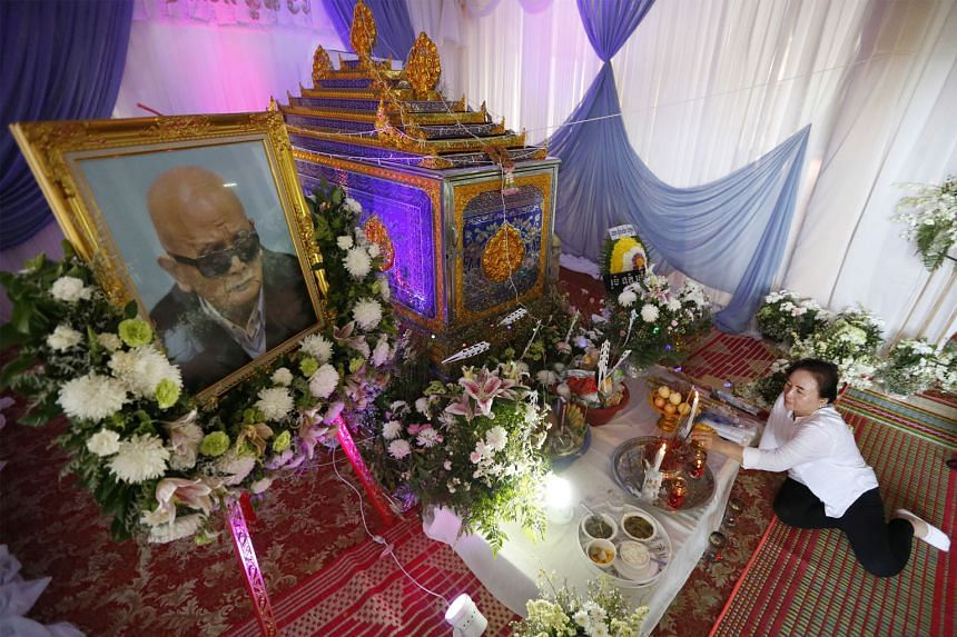 Nuon Chea's relative lighting incense in front of his coffin at a temple in Cambodia's western Pailin province on Thursday. The Khmer Rouge leader, who died on Sunday in a Phnom Penh hospital at age 93, was cremated yesterday.