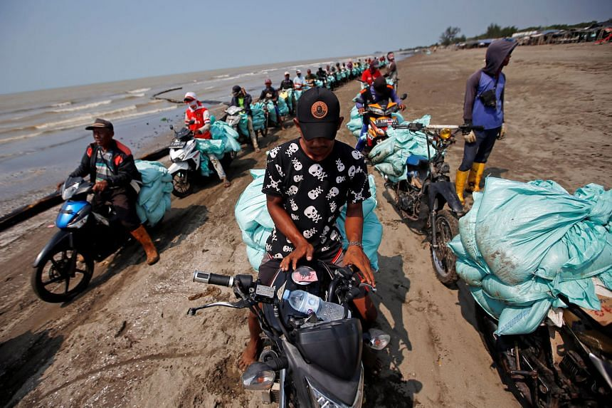 Workers with sacks of sand affected by an oil spill queueing to load them onto a truck at a beach in Karawang, West Java province, Indonesia, yesterday. The spill started on July 12, when state energy firm Pertamina was drilling at its YYA-1 well in
