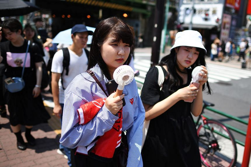 Two women using mini fans in Tokyo's Shin-Okubo district earlier this week. Temperatures in the Japanese capital have stayed above 31 deg C since July 24, exactly a year before the 2020 Olympic Games are set to open, rising to average daily highs of