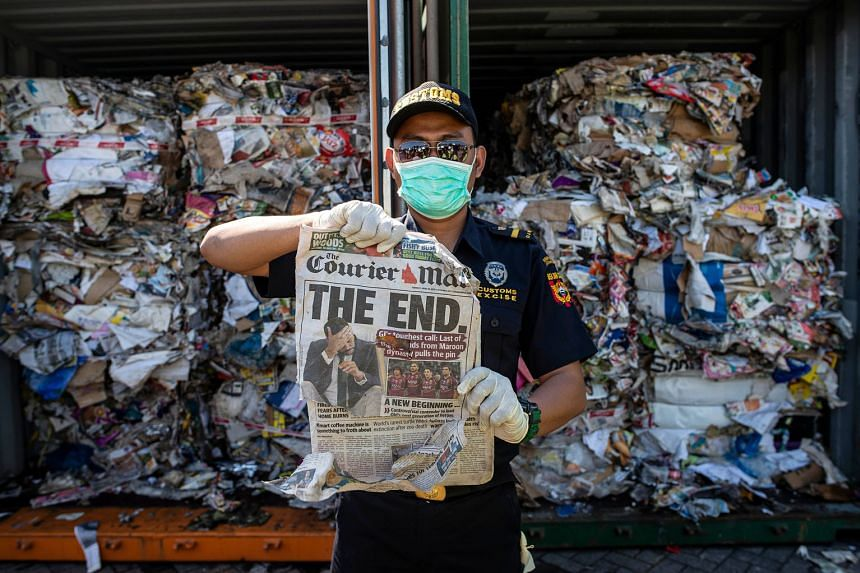 An Indonesian customs officer holding up a newspaper originating from Australia at a port in Surabaya on July 9. The container from which it was retrieved should have contained only waste paper, but the authorities also found hazardous materials and