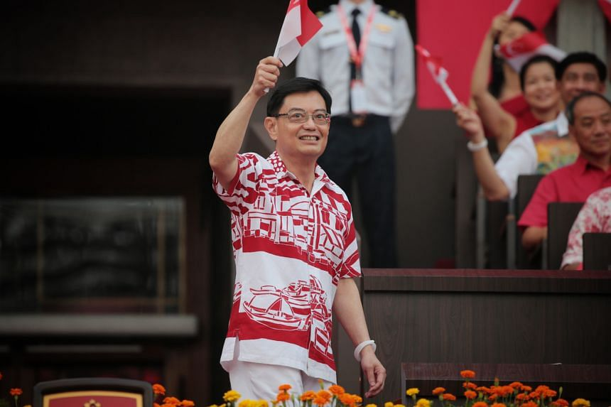 Deputy Prime Minister Heng Swee Keat waving a Singapore flag to the crowd as he arrives at the parade. Yesterday's parade was his first as DPM. He heads the 4G leadership team.