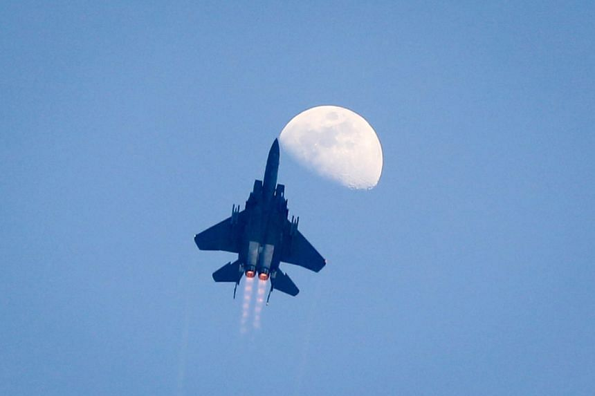 An aerial flypast is juxtaposed against the rising moon.