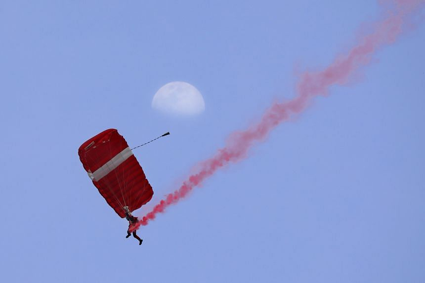 A member of the Red Lions team whizzes through the air amid cheers from the crowd at the Padang, leaving a trail of red in the sky.