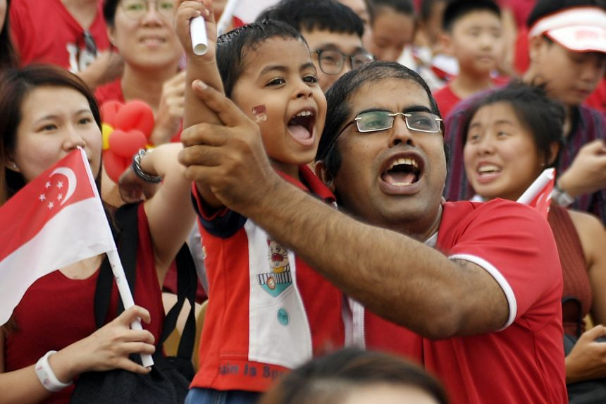 Mr Sandeep S. Thakkar, 39, and his four-year-old son Haricharana Thakkar enthusiastically waving the Singapore flag as they watched the parade.