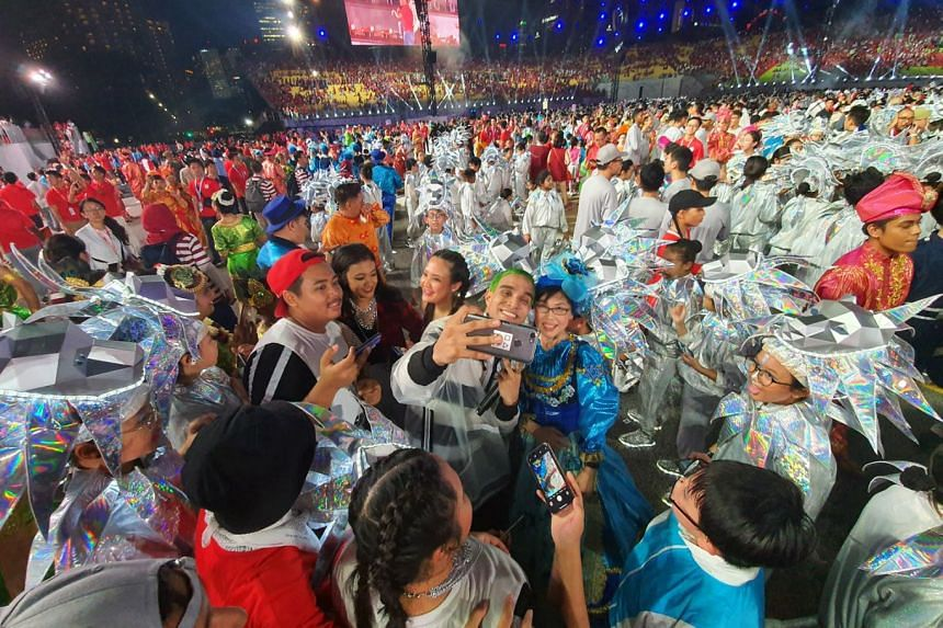 Performers, including rapper Yung Raja (with green hair), taking wefie photos with one another after the parade. This year's parade was the first held at the Padang since 2015, with previous years' NDPs held at the Marina Bay Floating Platform and th