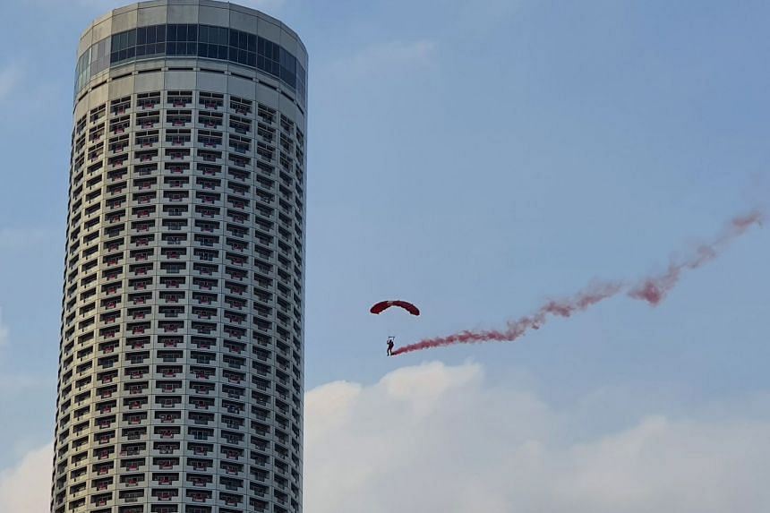 A Red Lion skydiver gliding through the air near Swissotel The Stamford as he prepares to land at the Padang. The team of nine parachutists jumped out of a helicopter from a height of 3,048m. This photo was captured using the Photo mode.