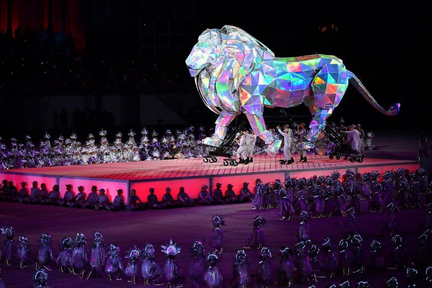 Children dressed in shiny silver lion costumes that light up in the dark perform as a majestic 6m-tall steel lion stands in the background, representing the vibrant future of Singapura - the Lion City.