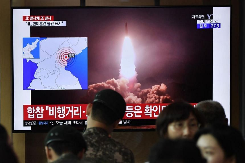 People watch a television news screen showing file footage of North Korea's missile launch, at a railway station in Seoul on Aug 10, 2019.