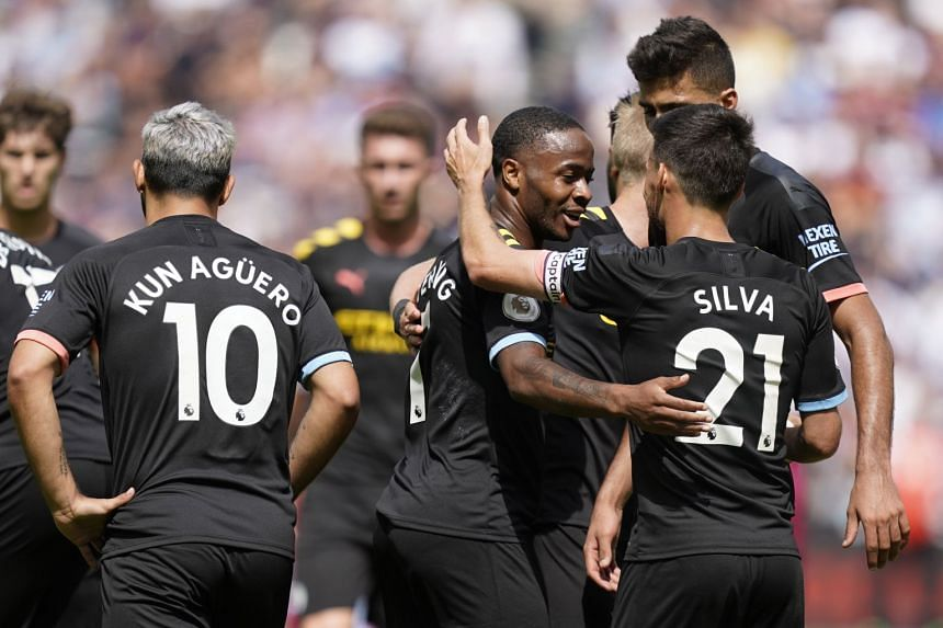 Manchester City's Raheem Sterling (centre) celebrates with team mates after scoring.