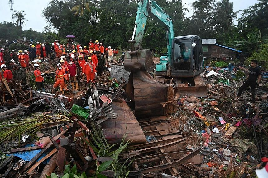 An excavator removing damaged structures yesterday after a landslide in Paung, Mon state.