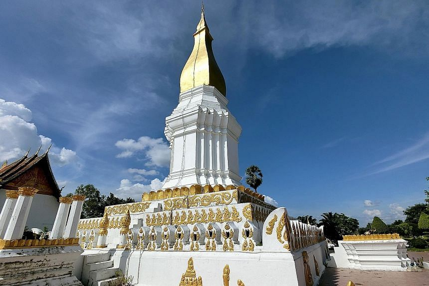 (Above) A traditional Baci ceremony at Wat Phabath in the Bolikhamxay Province, where a monk ties a piece of string on a person's wrist as a blessing.(Right) The Sikhottabong Stupa in Thakhek is a revered sacred site with an impressive 29m-tall golde