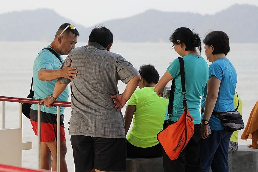 Family members of the missing pair keeping vigil. Conditions around Endau islands were rough when Mr Tan Eng Soon, 62, and Madam Puah Geok Tin, 57, went missing. Madam Puah's son was a participant in Friday's NDP. Search operations being carried out