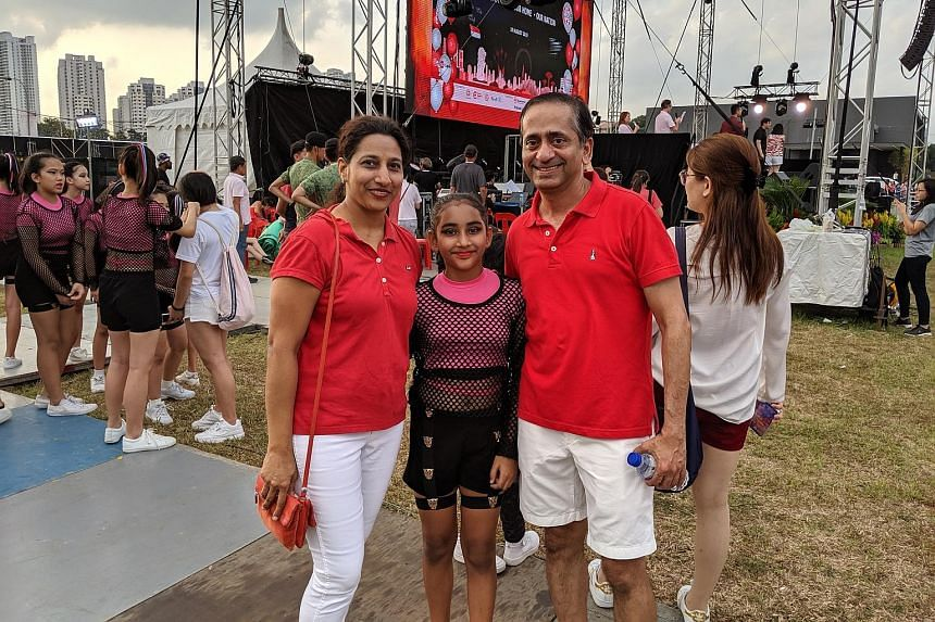 Mr Chetan Samel, 46, his wife Aparna, 42, and their daughter Saloni, 11, who performed at the National Day celebrations in Bishan yesterday. Mr Samel said he enjoyed the carnival as it was well organised and lively. Fireworks lighting up the sky near