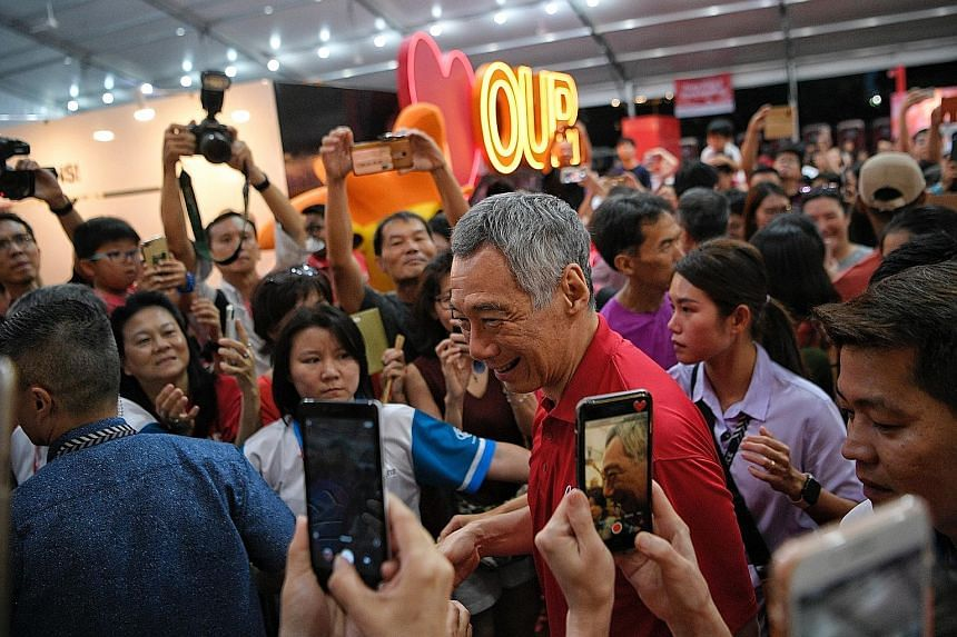 Above: Prime Minister Lee Hsien Loong mingling with the crowd during the National Day heartland celebration in Bishan yesterday.Right: Mr Lee, as a student in Catholic High School, leading the combined reed and brass band in the National Day Parade.
