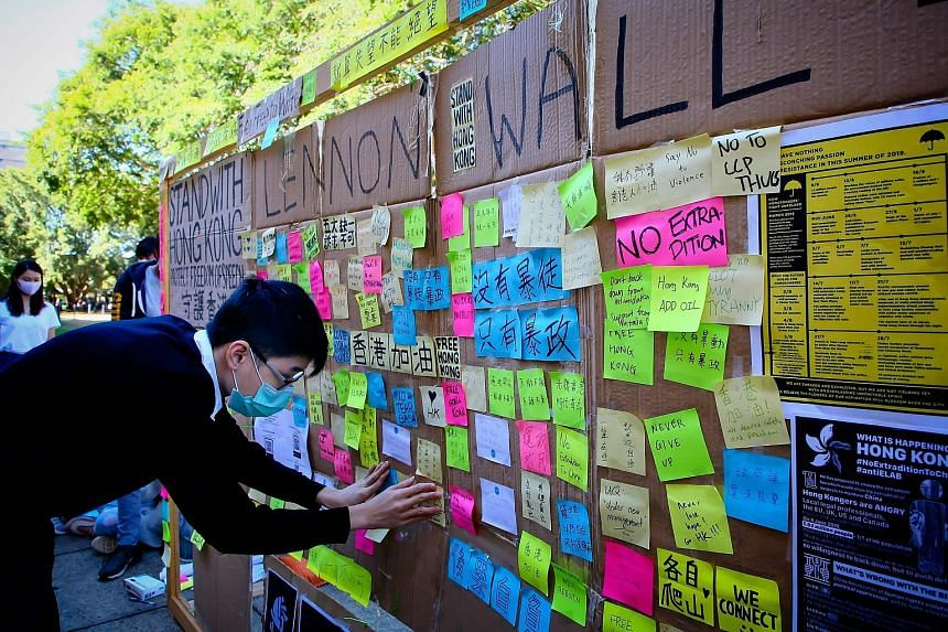 """A supporter of the Hong Kong pro-democracy protests posting a note on a makeshift """"Lennon wall"""" at the University of Queensland in Brisbane. Such actions have angered some mainland Chinese students, who have physically confronted protesters and torn"""