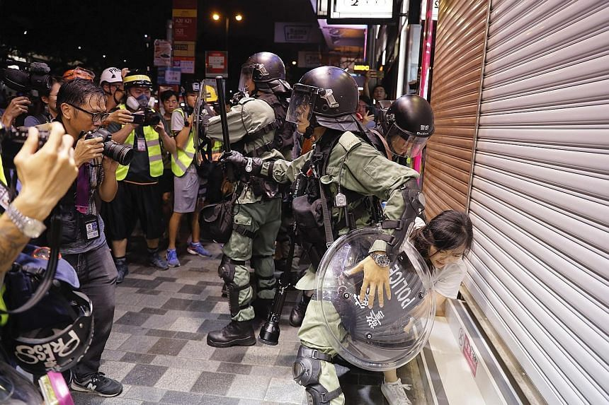 Police detaining a teenage girl during a confrontation with protesters in Hong Kong yesterday. More protests are expected today.