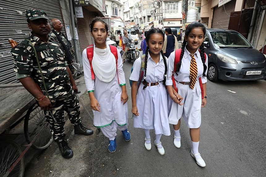 Indian paramilitary soldiers standing guard as children walked to school in Jammu yesterday. An additional 38,000 troops have been sent to the Kashmir valley, on top of the more than 70,000 already stationed there. A protester at a rally in Srinagar