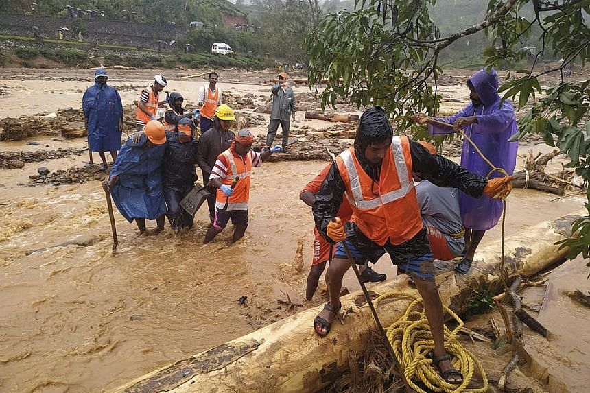 National Disaster Response Force personnel helping to evacuate flood victims to safer areas in Wayanad district, in the southern state of Kerala. PHOTO: ASSOCIATED PRESS