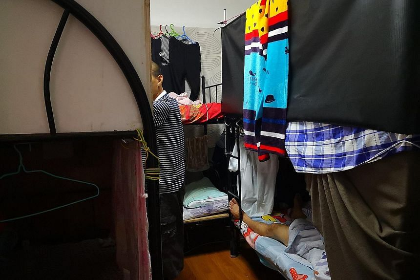 Sunday Times journalist Calvin Yang in a cramped room that is only 4 sq m in size. Located at People's Park Complex, it is let out for short-term stays. The room, which is for two occupants, can fit only a modest clothes rack and a bunk bed. There ar
