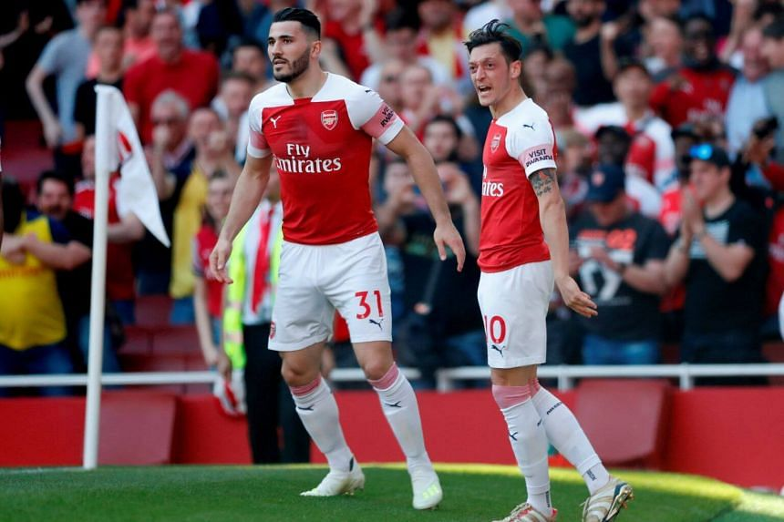 Arsenal's Mesut Ozil celebrates scoring their first goal with Sead Kolasinac against Crystal Palace during their Premier League match at the at Emirates Stadium in London, on April 21, 2019.