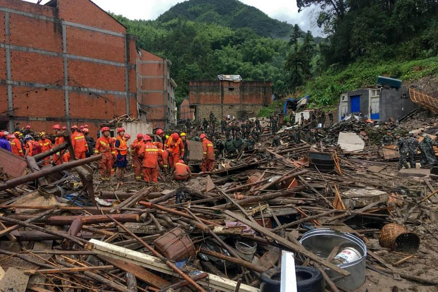 Rescuers looking for survivors in the rubble of damaged buildings after a landslide caused by torrential rain from Typhoon Lekima in Wenzhou, Zhejiang, on Aug 10, 2019.