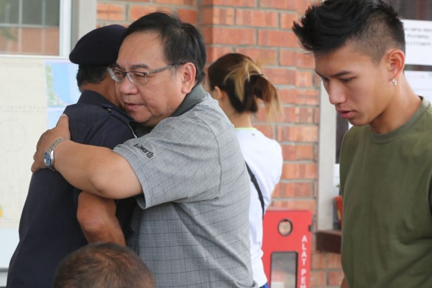 Mr Peng Mun Kit, the husband of missing kayaker Puah Geok Tin, receives a hug from Johor Malaysian Maritime Enforcement Agency director Aminuddin Abdul Rashid on Aug 10, 2019, in Mersing, Johor. Beside them is the couple's son Louis.