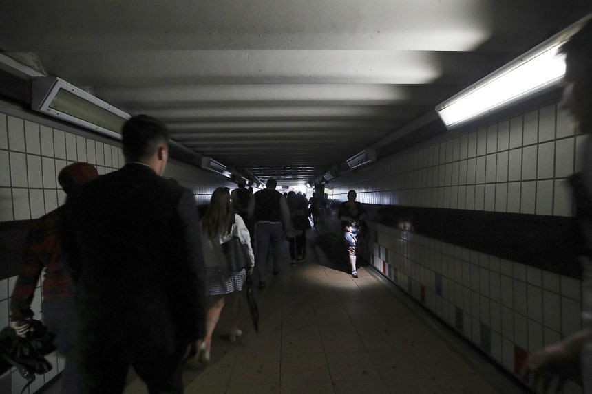 Commuters walking in near darkness at Clapham Junction station during a power blackout on Friday which left London and a large chunk of Britain without electricity, disrupting train travel and snarling rush-hour traffic.