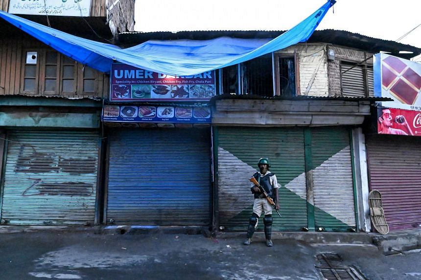 A security personnel member stands guard during a lockdown in Srinagar on Aug 10, 2019.