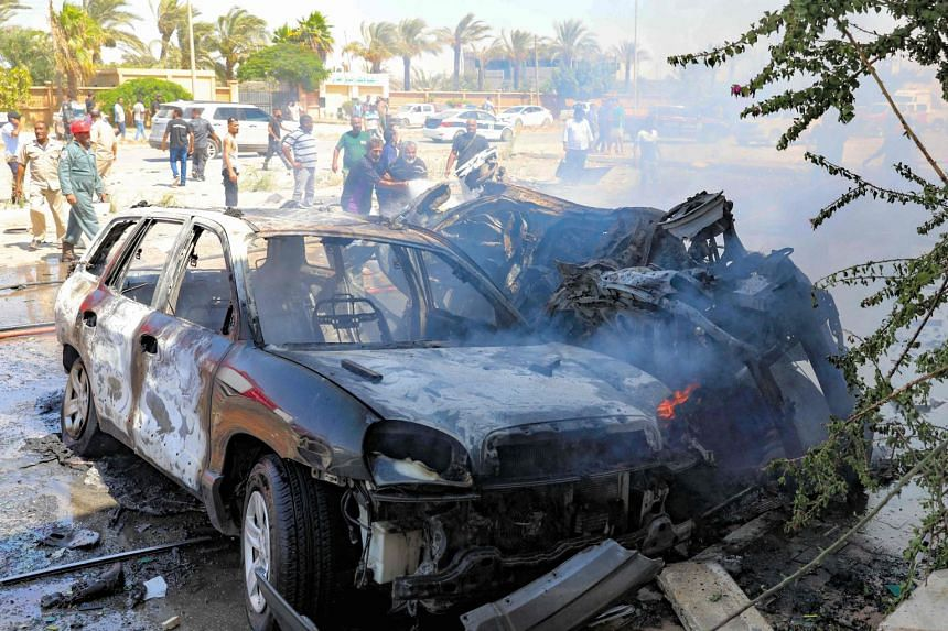 Libyans gather at the site of the car bomb attack in Libya's eastern city of Benghazi.