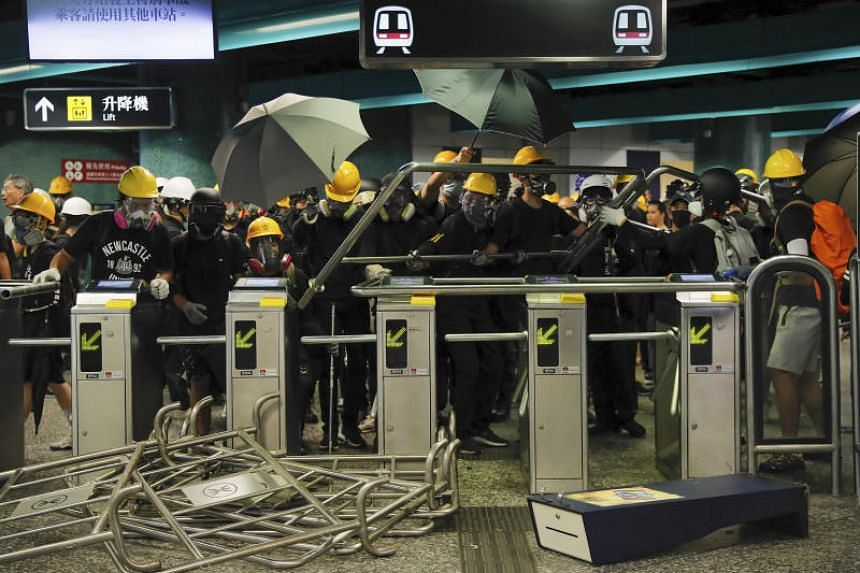 Protesters use steels barricades to form a defensive line inside the Quarry Bay MTR station as they face with riot police in Hong Kong on Aug 11, 2019.