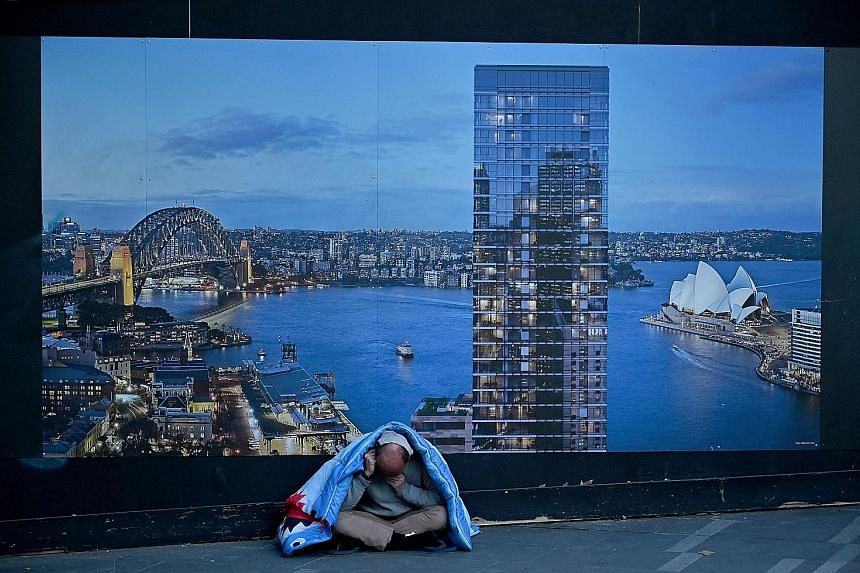 A homeless man in front of a construction site hoarding in Sydney. There has been a severe slump in building activity in the past year.