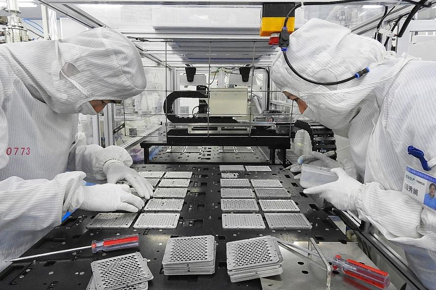 "A production line for mobile phone camera lenses at a factory in Lianyungang, Jiangsu province. China's industrial production and retail sales data for July are due out this week. The figures could ""influence broader sentiment surrounding Asian asset"