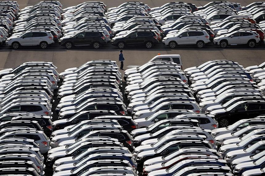 A file photo of new cars awaiting shipment at the port of Yokohama. Japanese carmakers may cut their profit forecasts if the yen's climb continues.