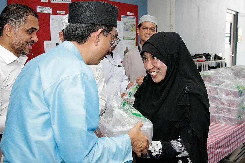 Jamiyah Singapore beneficiary Rahmah Jabbar receiving korban meat from Senior Parliamentary Secretary Faishal Ibrahim at Jamiyah Halfway House (Darul Islah) yesterday. ST PHOTO: JEREMY KWAN
