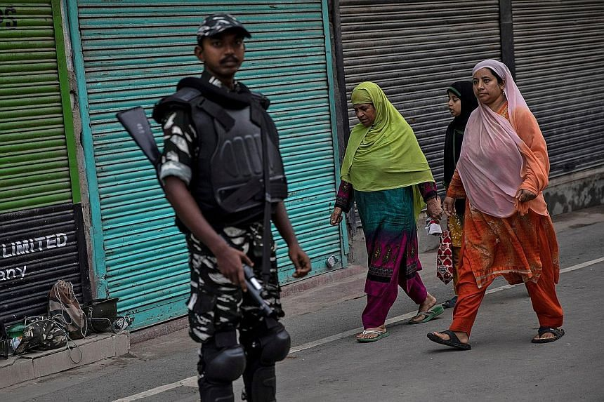 Kashmiri women yesterday walking past a security trooper in Srinagar after restrictions were eased for today's Eid al-Adha festival. The restrictions were imposed after India revoked Kashmir's special status.