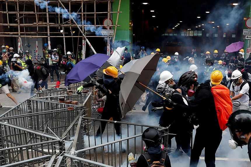Protesters responding to tear gas fired by police during a rally in Hong Kong's Sham Shui Po area yesterday. Tear gas was even used indoors, at a train station in Kwai Fong, though it is rare for police to do so. Beijing says criminals and agitators
