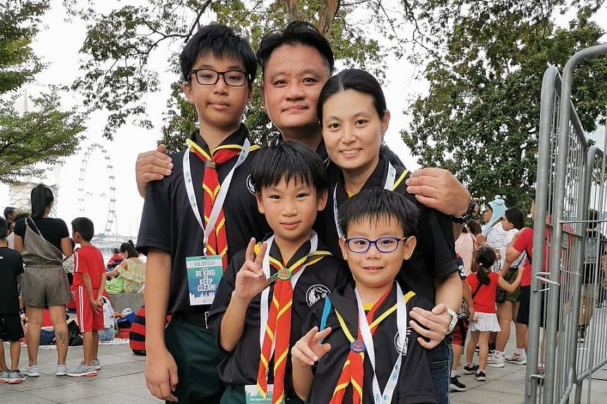 Mr Caleb Teo, his wife, Ms Shu Yi Ping, 41, and their sons (from left) Isaiah, Zechariah and Jedidiah went to the Padang area not to catch the NDP but to help keep the place litter-free. PHOTO: NATIONAL ENVIRONMENT AGENCY