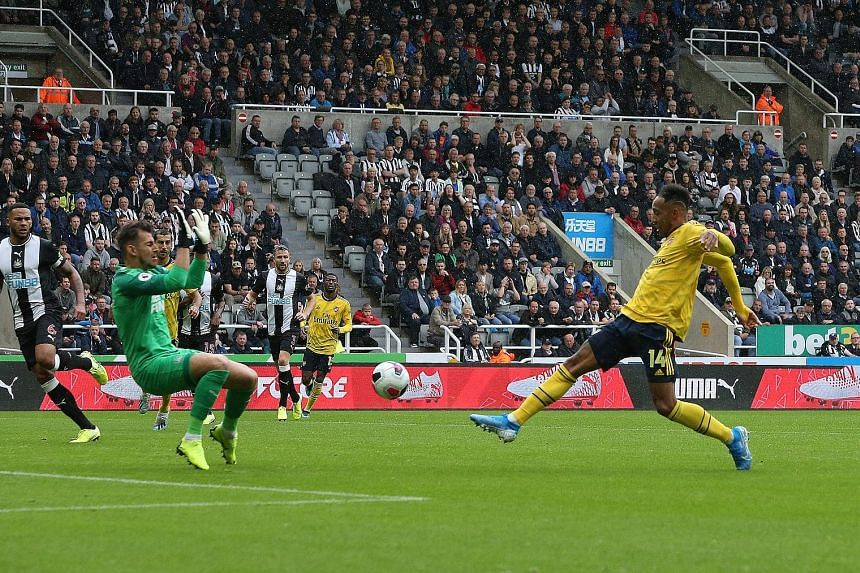 Arsenal's Pierre-Emerick Aubameyang scoring the only goal of the game past Newcastle goalkeeper Martin Dubravka as the Gunners made a winning start to their Premier League campaign at St James' Park yesterday. PHOTO: EPA-EFE