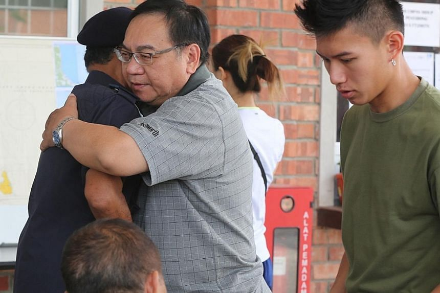 Mr Peng Mun Kit, the husband of missing kayaker Puah Geok Tin, receiving a hug from Johor Malaysian Maritime Enforcement Agency director Aminuddin Abdul Rashid yesterday in Mersing, Johor. Beside them is the couple's son Louis. Above: Madam Puah Geok