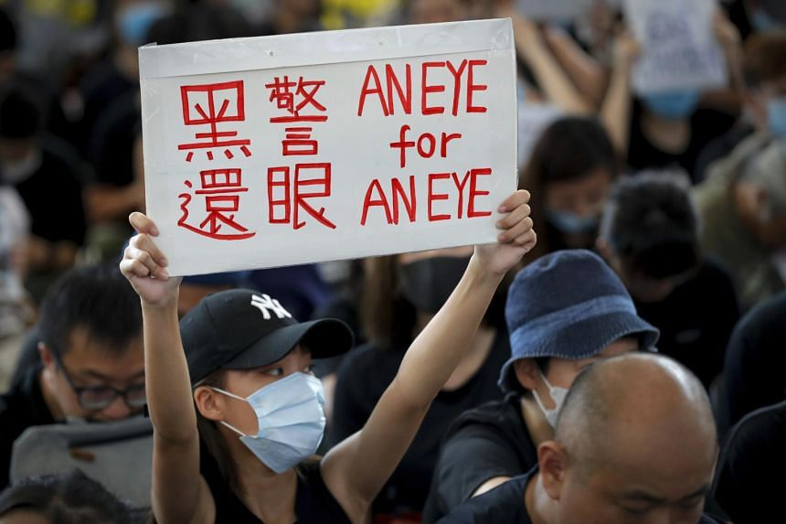 A woman holds a placard during a sit-in protest at the arrival hall of the Hong Kong International Airport on Aug 12, 2019.