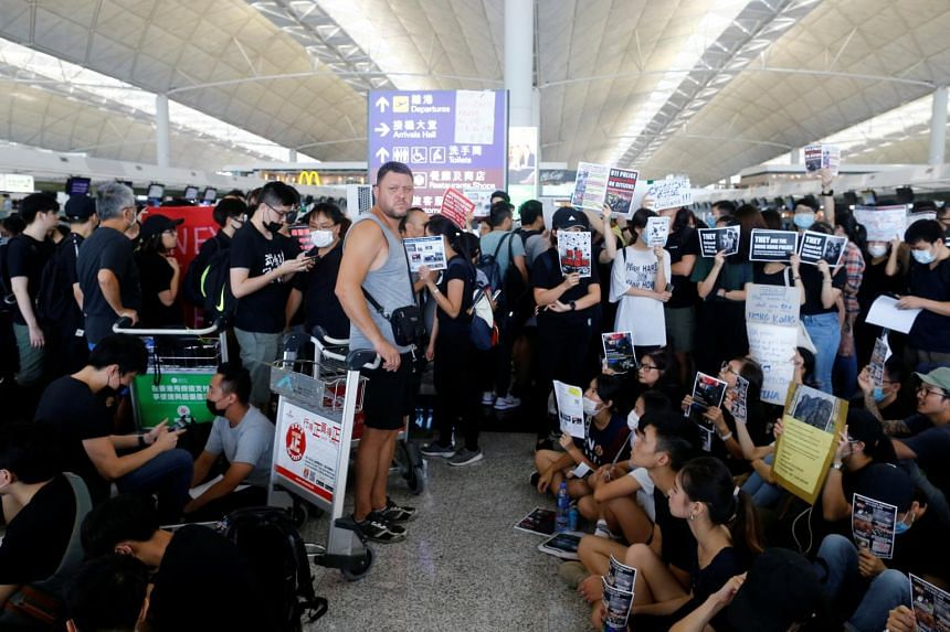 A passenger waits at the departure hall as anti-extradition bill protesters rally at of Hong Kong airport on Aug 12, 2019.