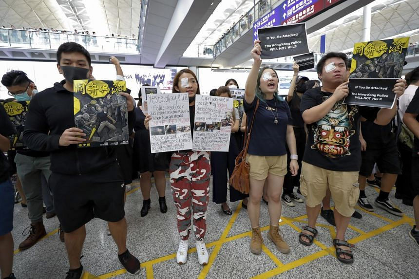 Protesters hold signs while wearing eyepatches during a protest at the arrival hall of the Hong Kong International airport on Aug 12, 2019.