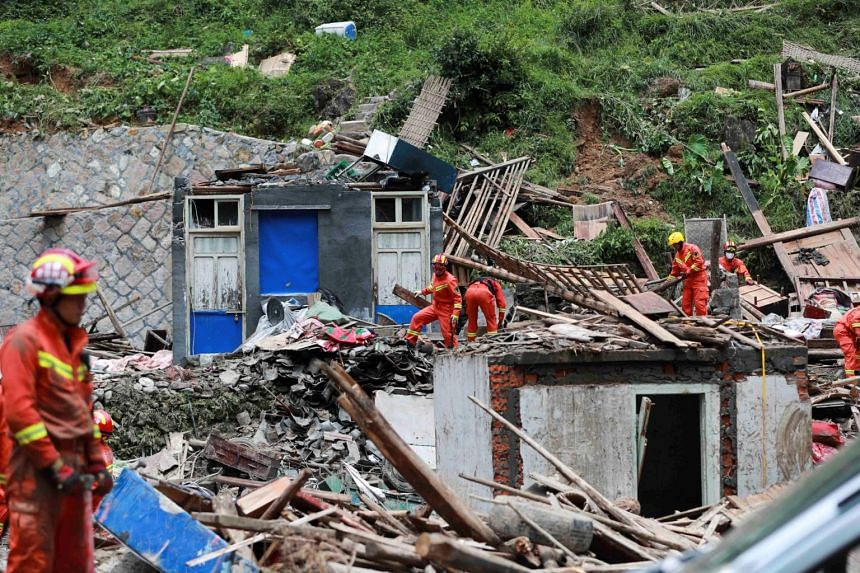 Firefighters search for survivors in collapsed houses damaged by a landslide after Typhoon Lekima hit Shanzao village in Wenzhou, Zhejiang, on Aug 11, 2019.