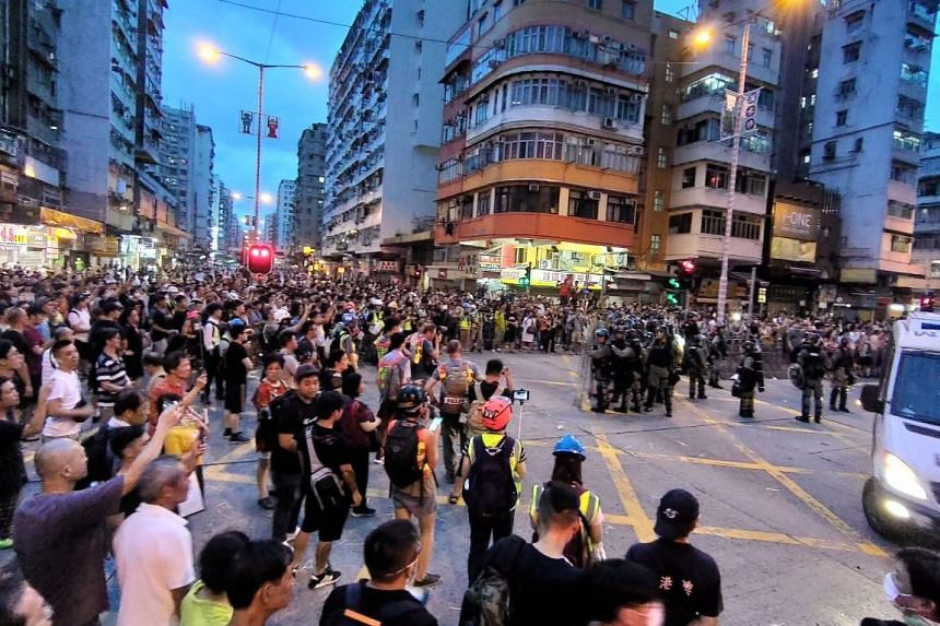 Police face a massed crowd of locals at the intersection of Cheung Sha Wan Rd and Yen Chow St in the Sham Shui Po neighbourhood after arresting a protester on Aug 11, 2019.