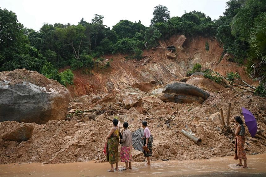 Residents look at an area affected by a landslide in Mutkyi, Myanmar, on Aug 12, 2019.