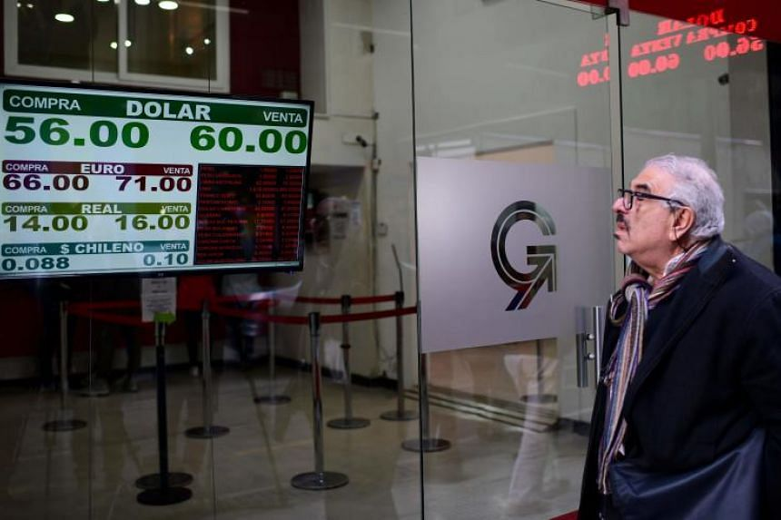 Currency exchange values are displayed on the buy-sell board of a bureau de exchange in Buenos Aires, on Aug 12, 2019.